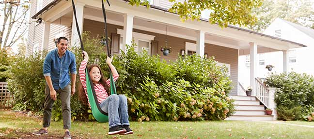 father pushing daughter on swing in front yard